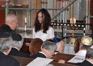 A fiatal hölgy felolvassa az áldozatok nevét, akik gyülekezet tagjai voltak. Ezalatt a hitközség egyik rangidőse pedig felkelvén a helyéről, gyertyát gyújt a halottakért