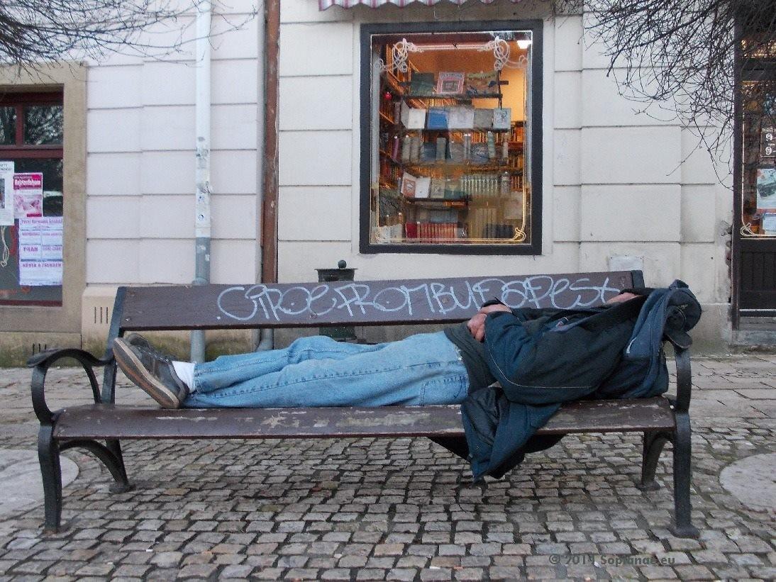 Obdachloser auf Bank im Dezember